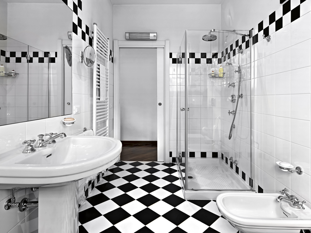 Black and white bathroom with extensive white tiling offset with black and white checkered strip on top of wall and on the floor.