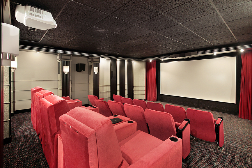 Home theater in luxury home with red chairs