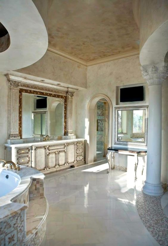 Palatial bathroom featuring mosaic tile around the mirror to the wall finish and marble Corinthian columns