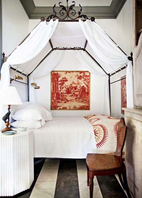 All white eclectic bedroom with conopy bed and striped flooring.