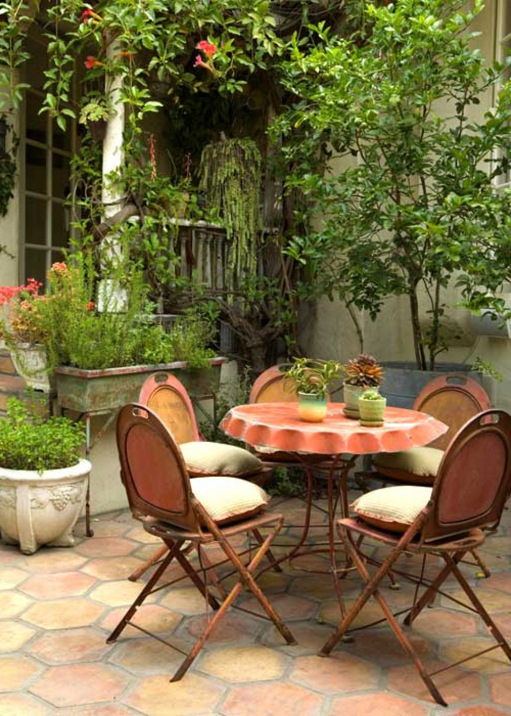Beautiful patio dining area with rustic metal chairs and small round table best for small spaces.