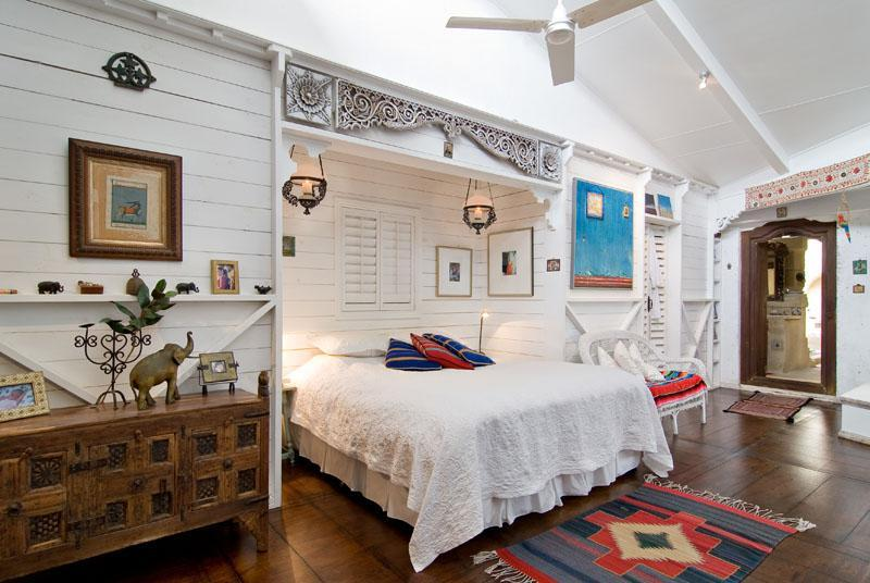 Eclectic bedroom with traditional wooden furniture and dark wood flooring.