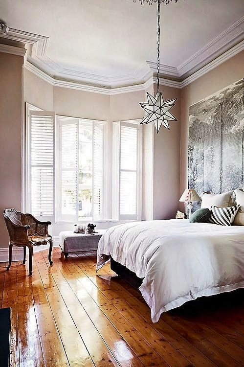 Fantastic eclectic bedroom with vintage style wooden flooring and chic furniture.