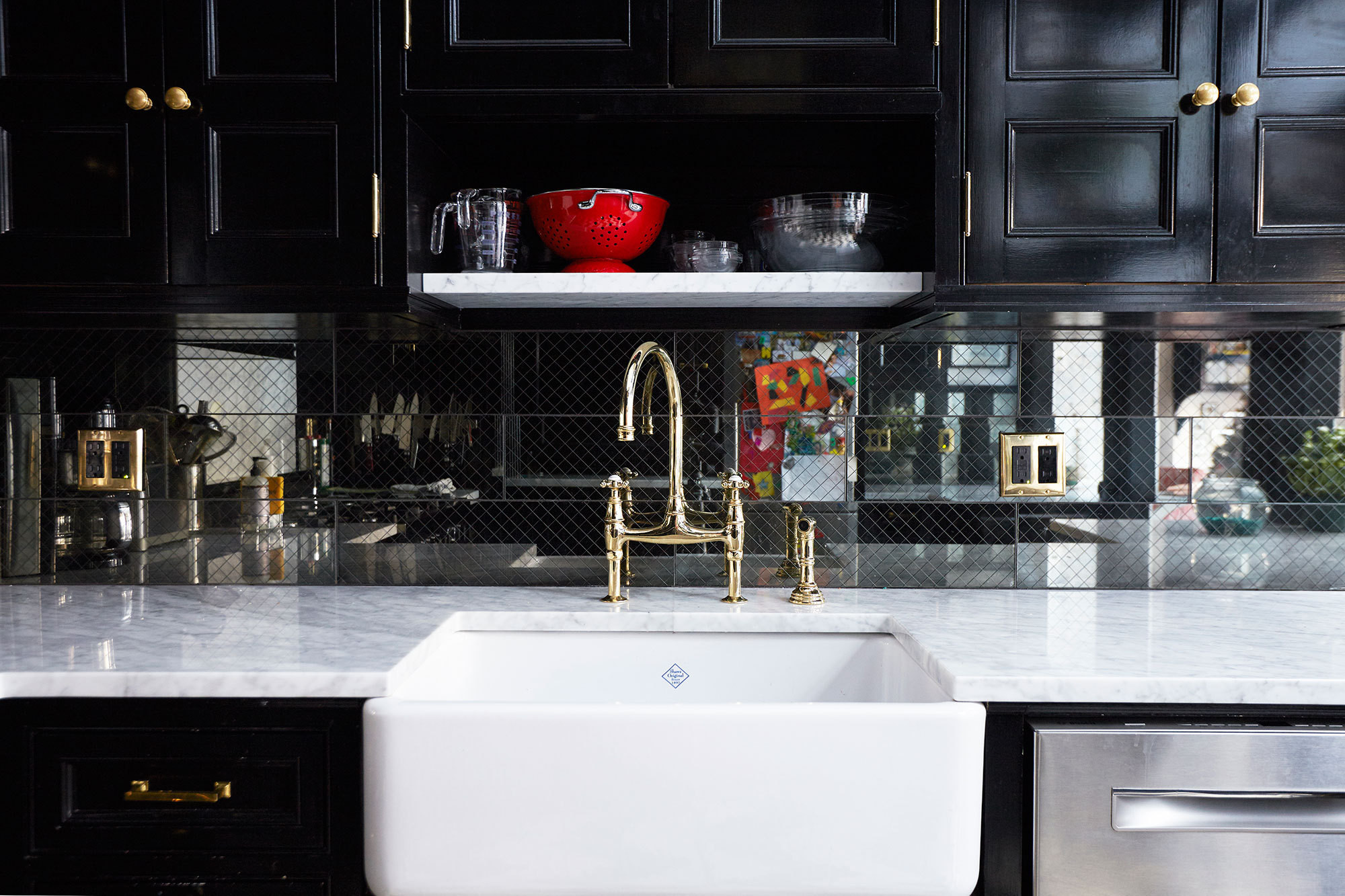 The high-glosss black and brass accented brownstone kitchen