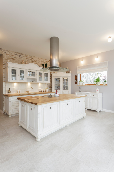 Whimsical ornate white kitchen with large island