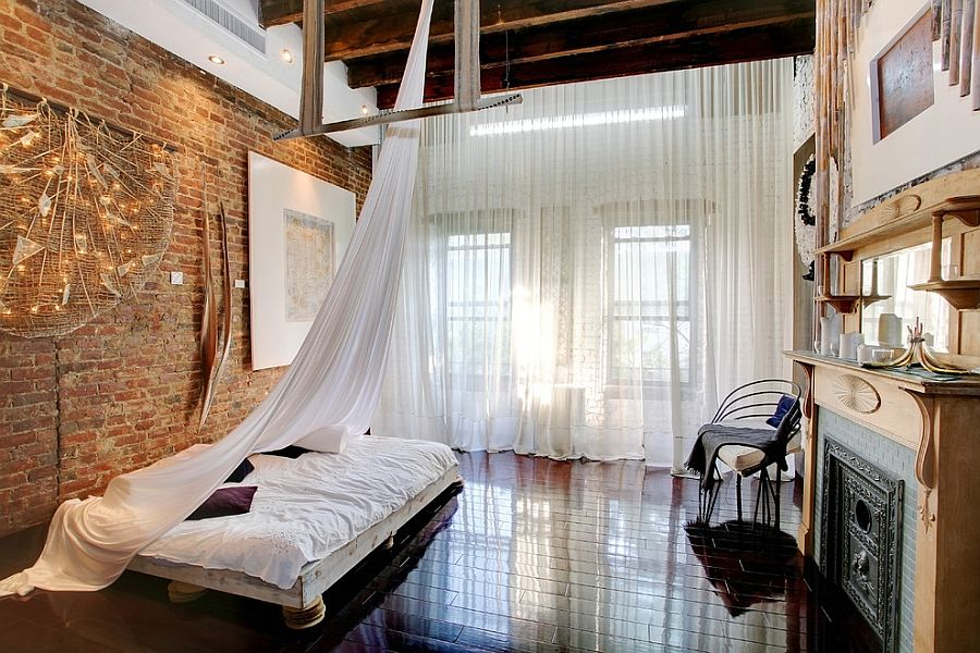 exposed-brick-walls-behind-bedroom-with-sheer-curtain