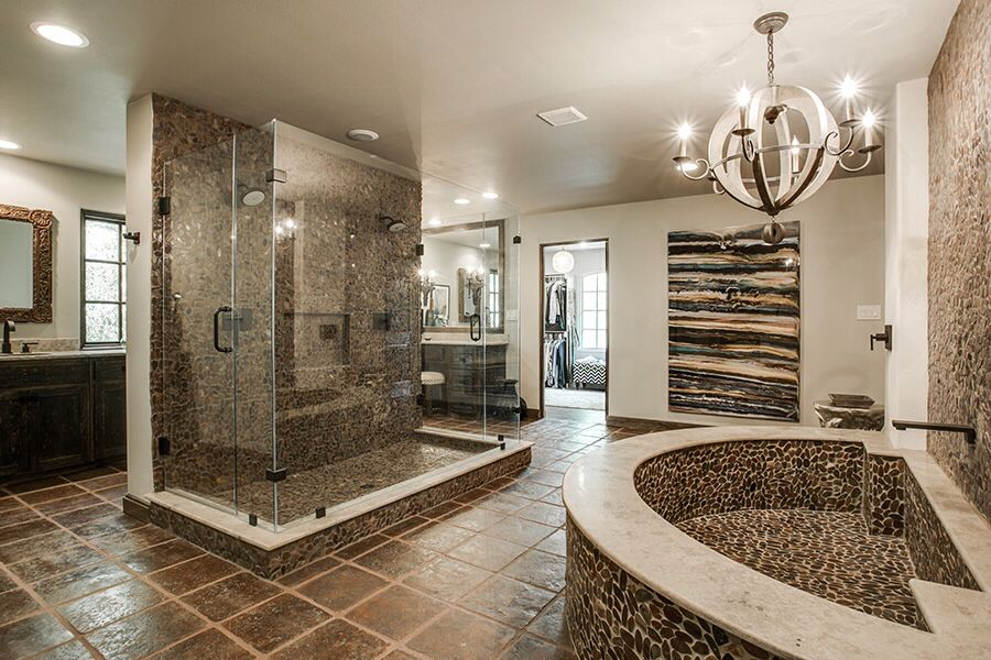 Rustic master bathroom with a chandelier